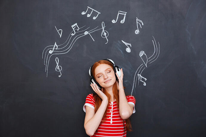 Relaxed smiling beautiful young woman listening to music in headphones over chalkboard background-1